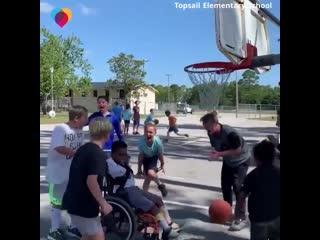 Boys help friend in wheelchair make a basket